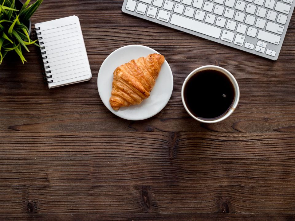Picture of a notebook, croissant, coffee, and keyboard.